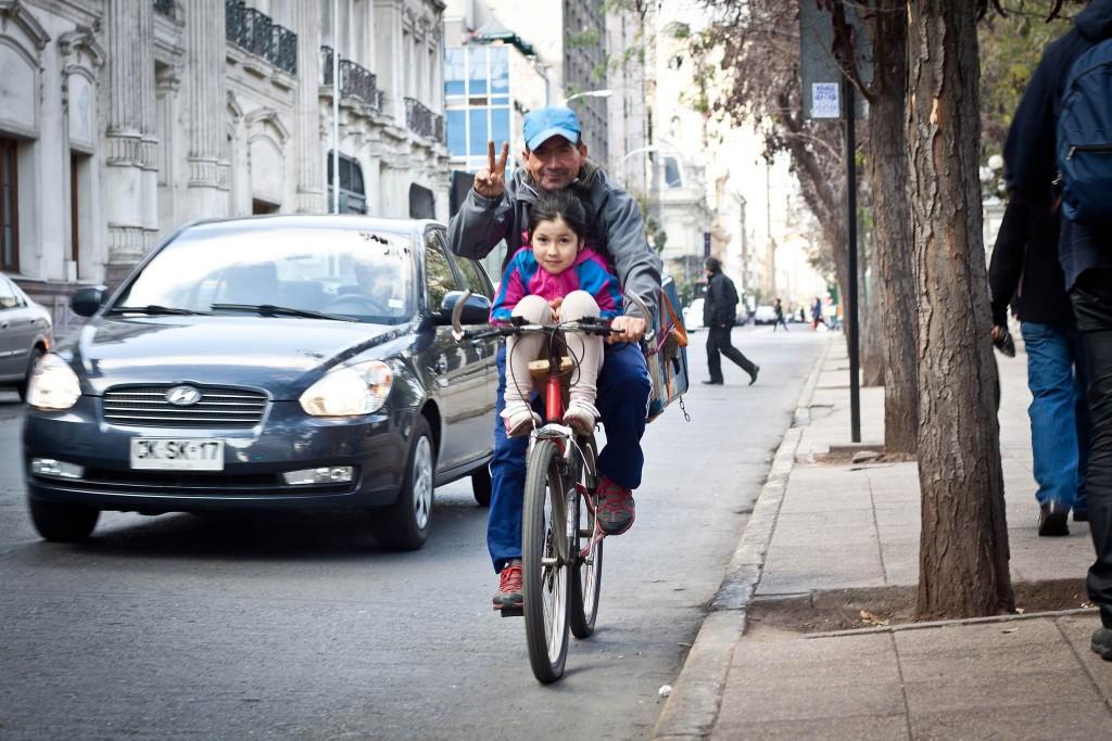 Un hombre y una niña comparten la bicicleta en Santiago