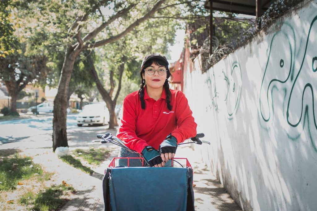 Camila posa con su bicicleta de correos